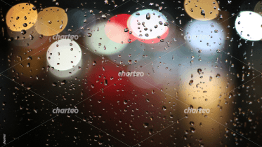 Blurred city lights through rainy window pane