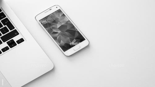 Smartphone lying on a desk next to laptop