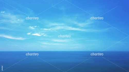 Blue ocean and sky with scattered clouds