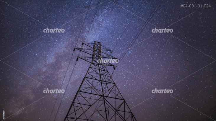 Transmission tower with power lines beneath starry sky