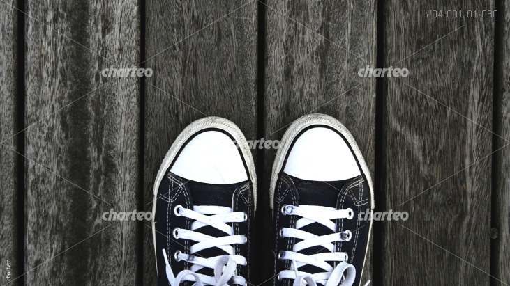 Pair of sneakers on wooden planks