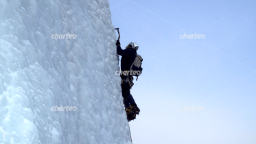Rock climber cresting iceberg with an ice pick