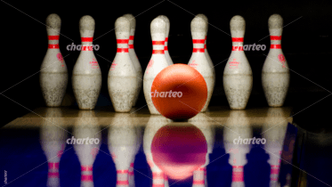 Bowling ball rolling towards pins in bowling alley