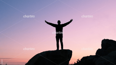 Silhouette of man standing on rock in sunset