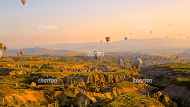 Numerous hot air balloons flying over plateau landscape