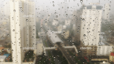 Blurred view on city through rainy window pane