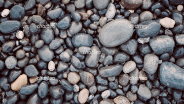 Mass of wet pebble stones covering the ground